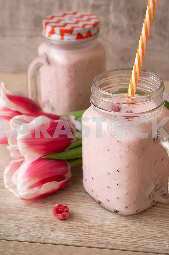 Pink raspberry cream smoothie in mason jar and tulips — Image 83051