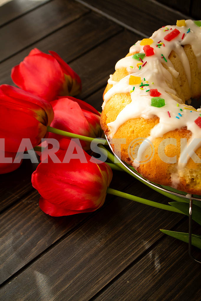 Easter yeast cake or babka covered with icing and decorated with colorful decoration on a dark wooden table and bright tulips — Image 83058