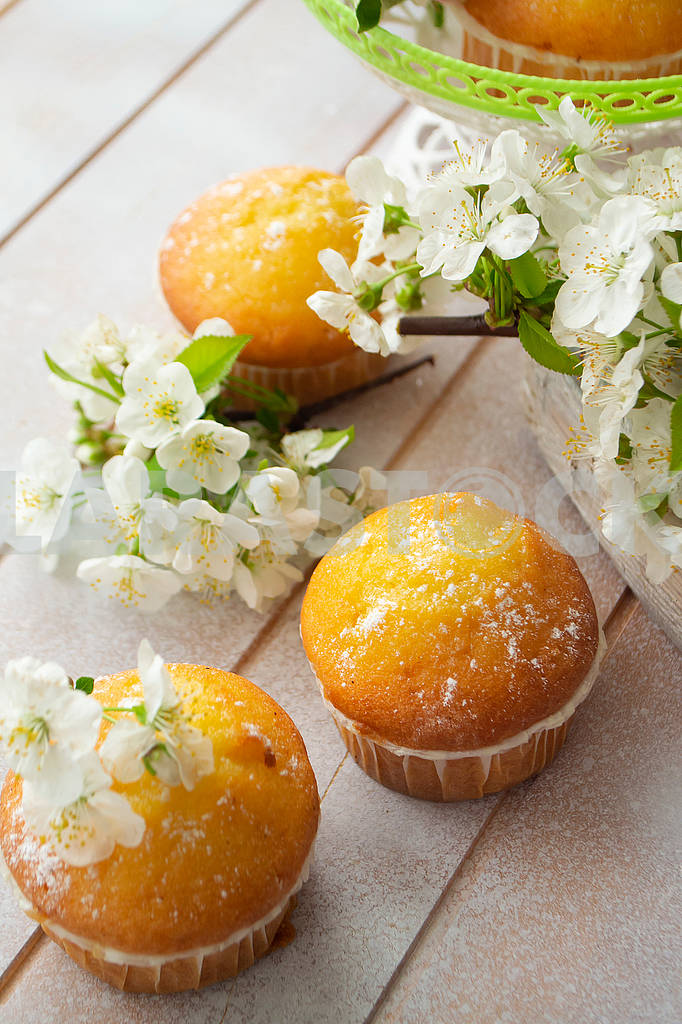 Golden muffins with cherriy flowers on shabby table — Image 83116