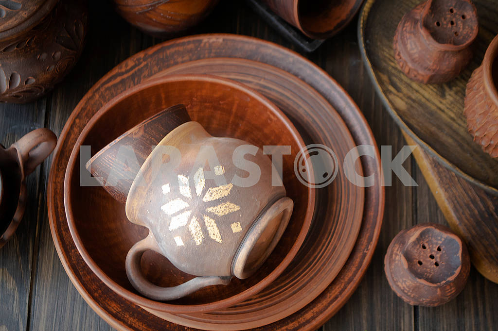 Rustic handmade ceramic clay brown terracotta cups, plates, bowls. Top view. — Image 83226
