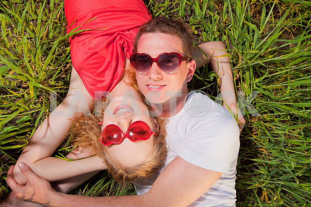 Beautiful young couple sunglasses lies in on grass — Image 8357