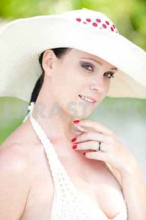 Portrait of beautiful young girl in white hat