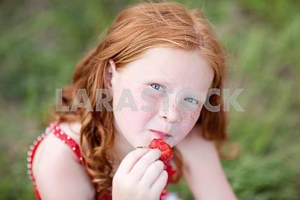 Девушка , которая ест клубнику . Мягкий фокус. Сосредоточьтесь на глаза .