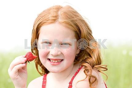 Девушка , которая ест клубнику . Мягкий фокус. Сосредоточиться на глаза .