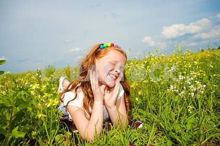 Little beautiful girl outdoor. Lay on the green grass.