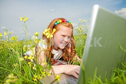 Girl with laptop resting on meadow.