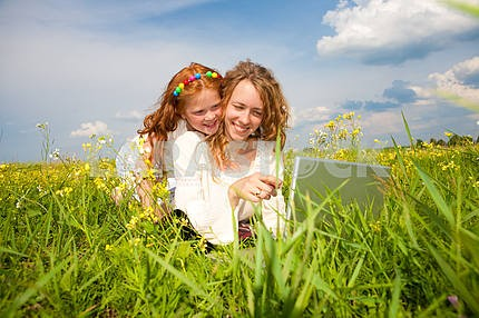 Mother and daughter lay on a grass with a notebook