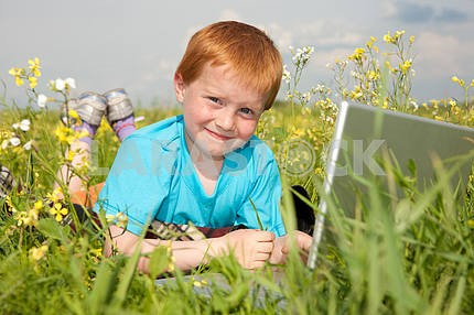 Smiling child with laptop computer on meadow