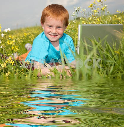 Smiling child with laptop computer on meadow. Reflected in Water