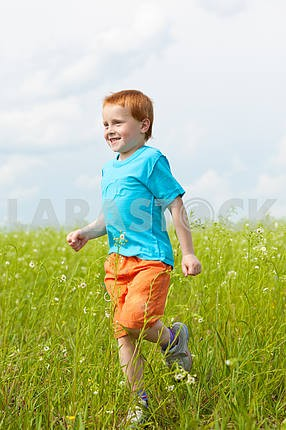 Happy boy run against beautiful sky