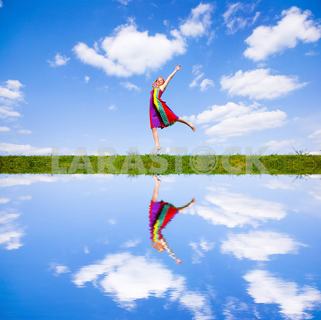 Happy girl jumping together on green meadow. Reflected in water — Image 8798