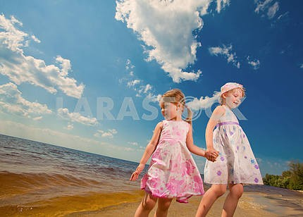 Two cute sisters play in waves on sea