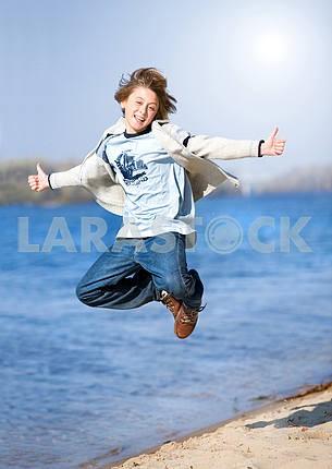 Счастливый прыжков мальчик на пляже