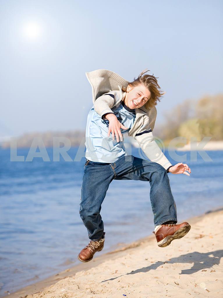 Счастливый прыжков мальчик на пляже — Изображение 8987