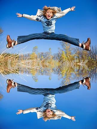 Счастливый прыжков мальчик. Отражение в воде
