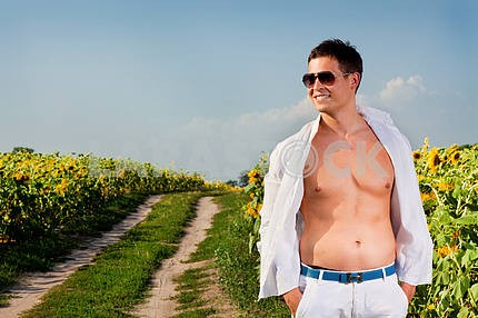 Счастливый молодой человек в поле подсолнухов