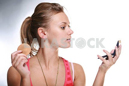 Pretty woman applying make-up with powder.