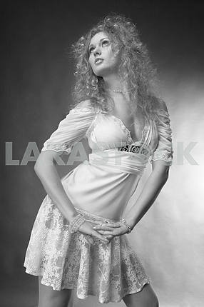 Beautiful Young Woman in a white dress. In the studio.