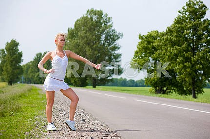 Woman in the road auto-stop under the blue sky and green trees