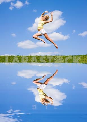 Счастливый молодая женщина прыгает . Отражение в воде .
