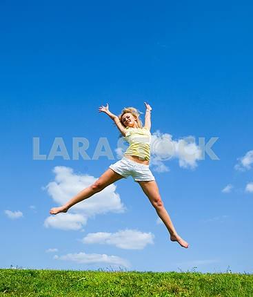 Счастливый молодая женщина прыгает в поле