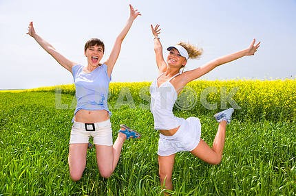 Two beautiful women in white clothes jumping in field