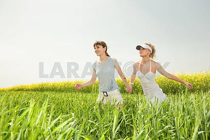 Two young girls are happily jumping on grass
