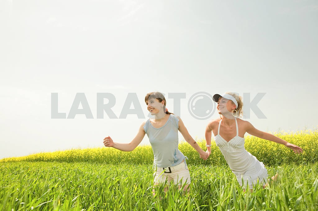 Two young girls are happily jumping on grass — Image 9264