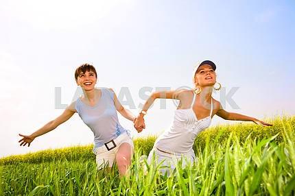 Две красивые женщины в белых одеждах идут на желтых цветов