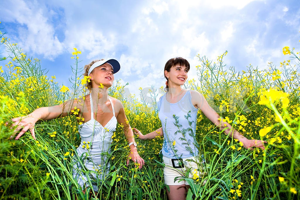 Two beautiful girl in white clothes go to the yellow flowers — Image 9269