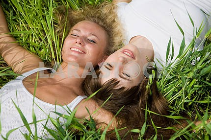 Two beautiful young women lay on green grass outdoors