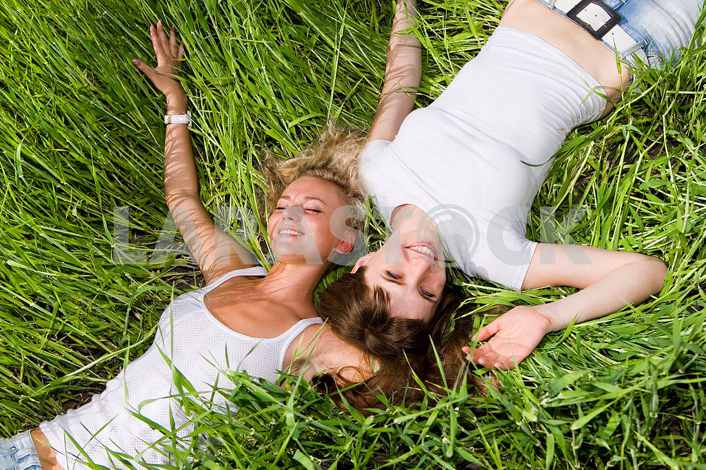 Two beautiful young women lay on the green grass outdoors. — Image 9282