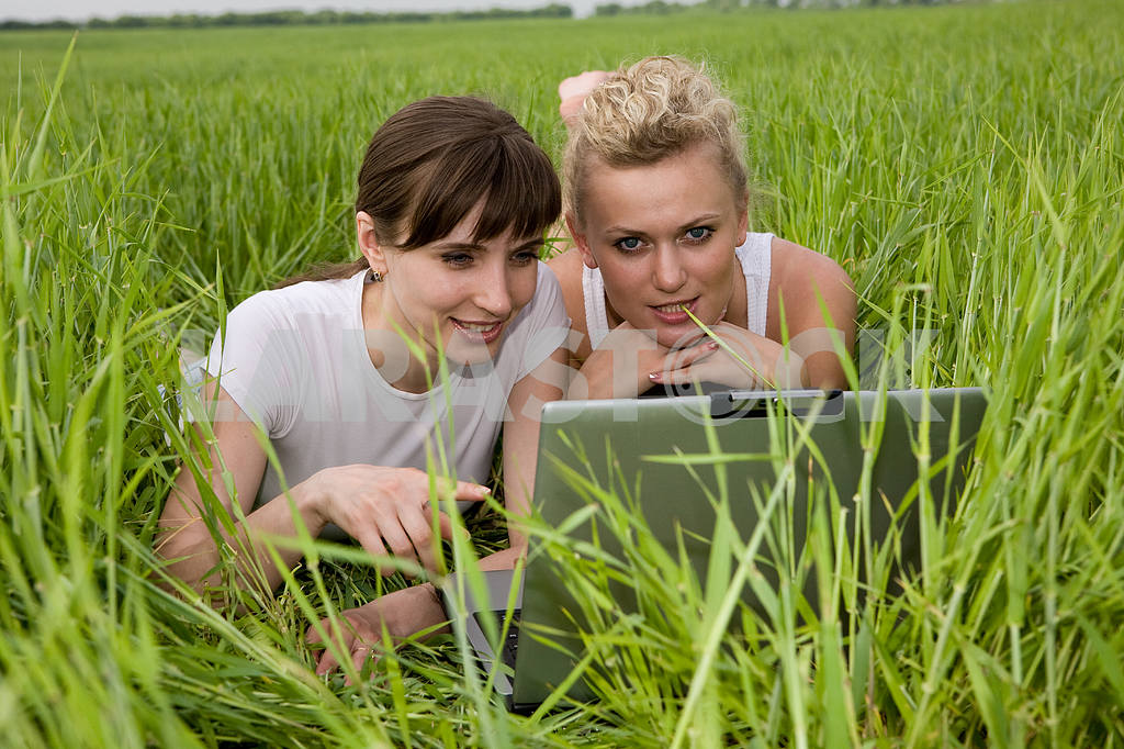 Two beautiful girls in white clothes are laughing near laptop co — Image 9285