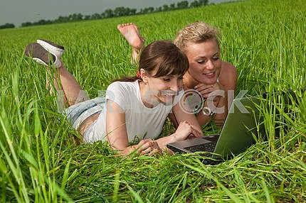 Two beautiful girls in white clothes are laughing and looking at