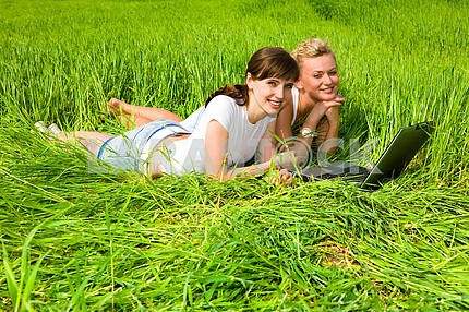 Two beautiful girls in white clothes are laughing near laptop co