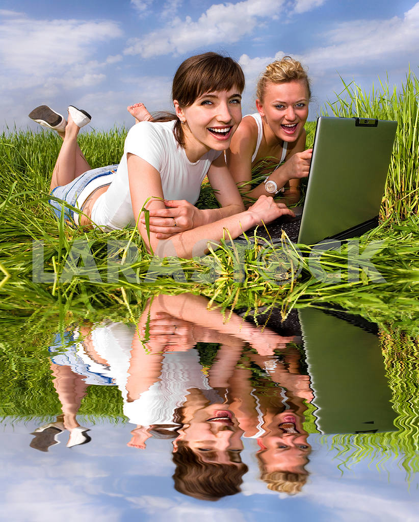 Two beautiful girls in white clothes are laughing near laptop co — Image 9302