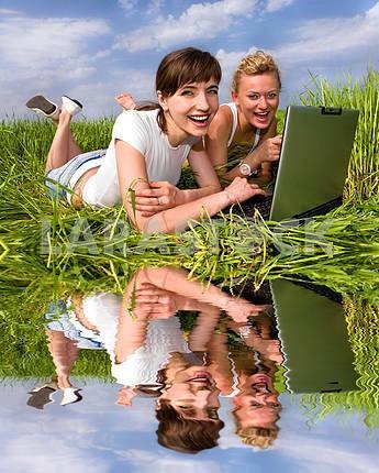 Две красивые девушки в белых одеждах смеются рядом с ноутбуком со