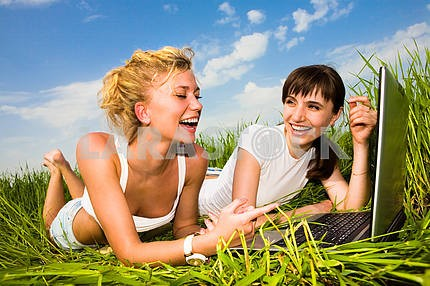 Two beautiful girl in white clothes on a laptop computer outdoor