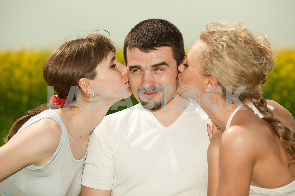 Two beautiful girls kissing on the cheek guy — Image 9334
