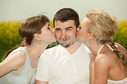 Two beautiful girls kissing on the cheek guy