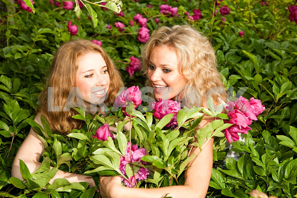 Two happy young women in flowers — Image 9336
