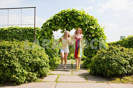 Two happy young women are runing in a park