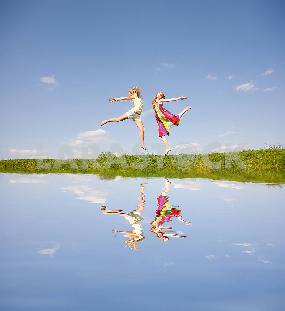 Two happy girls jumping — Image 9367