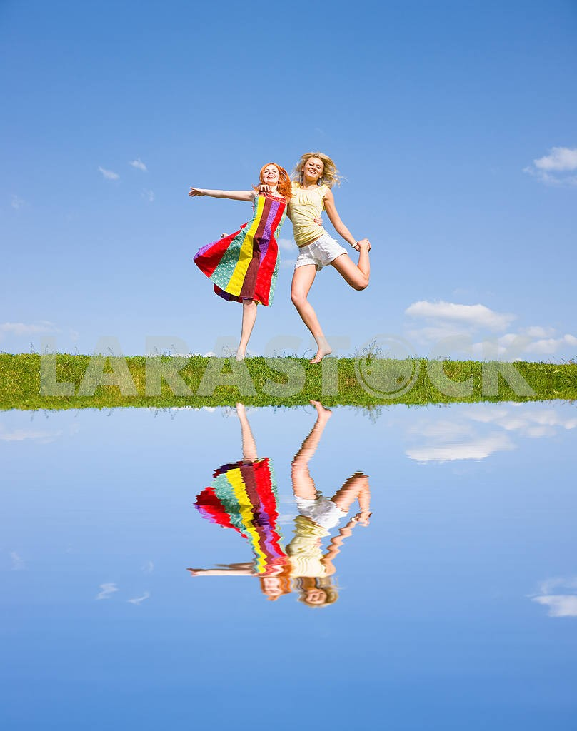 Two happy girls jumping together on green meadow. — Image 9369