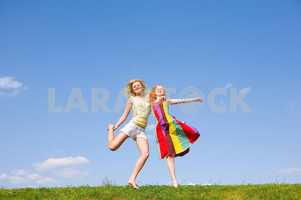 Two happy girls jumping together on green meadow. — Image 9370