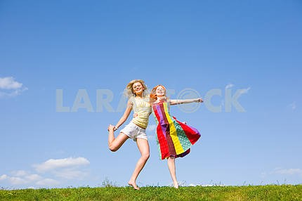 Two happy girls jumping together on green meadow.