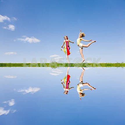 Two happy girl jumping together on green meadow. Reflected in wa