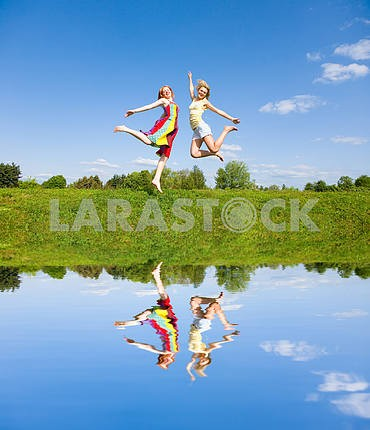 Two happy girls jumping together on green meadow
