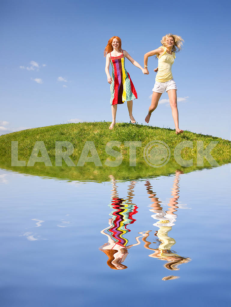 Two happy girls fleeing on a meadow. Reflected in water — Image 9380
