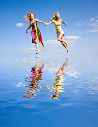 Two happy girls fleeing on a water under the blue sky.
